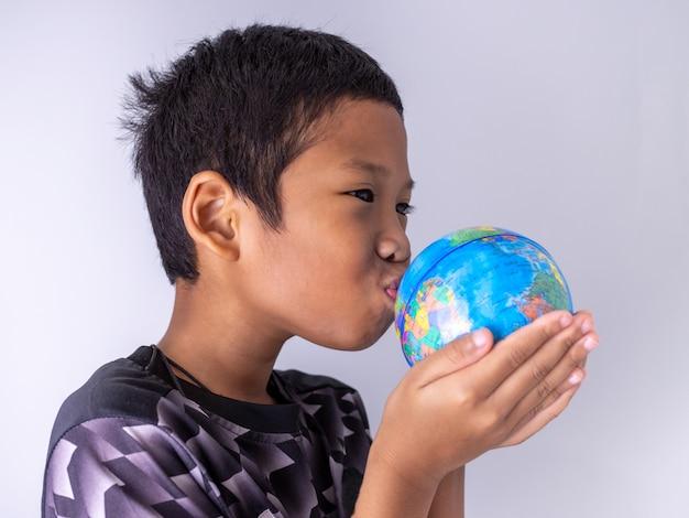 Een jongen overhandigt de wereldbol en kust hem op de wereldbol toon de kracht van de nieuwe generatie om onze wereld verder te ontwikkelen