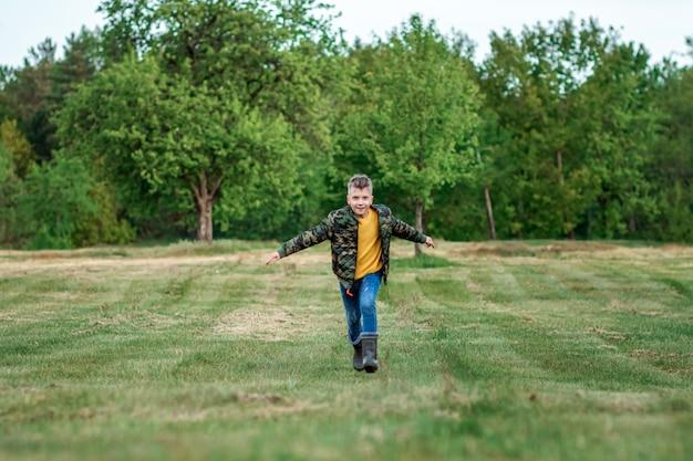 Een jongen rent met uitgestrekte armen over het veld