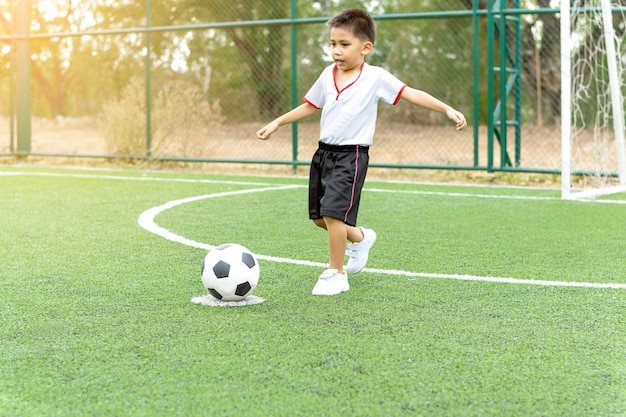 Een jongen rent om een voetbal te schoppen op het voetbalveld.