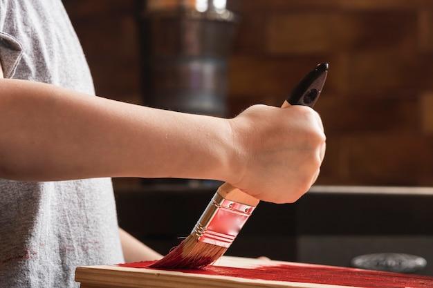 Een jongen schildert een houten nep met een penseel in rood in een landhuis