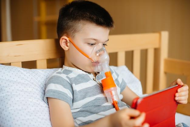 Een jongen speelt op een tablet tijdens een longinhalatieprocedure.