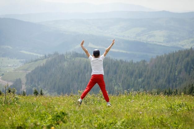 Een jongen springt op de top van een berg van vreugde om vrijheid te voelen en van de schoonheid die hij zag