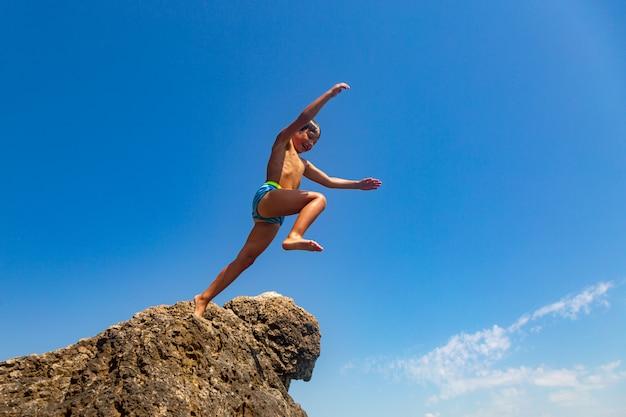 Een jongen springt van de klif in de zee op een warme zomerdag. vakantie op het strand. actief toerisme en recreatie