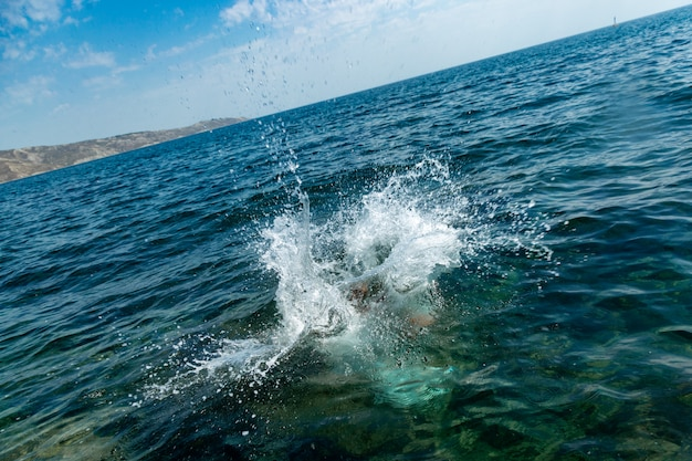 Een jongen springt van de klif in zee met grote waterspatten op een warme zomerdag. vakantie op het strand. actief toerisme en recreatie