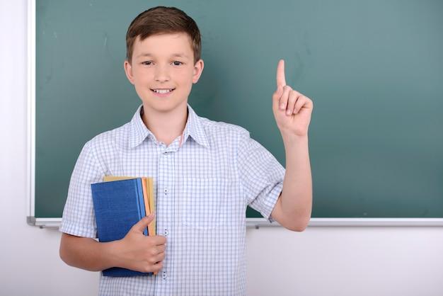 Een jongen staat bij het bord en hief zijn vinger op.