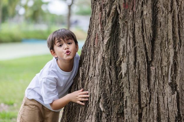 Een jongen staat een grote boom knuffelen en speelse uitdrukking verstoppertje. vervuilingsprobleem.