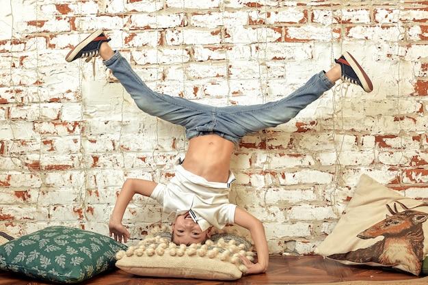 Een jongen staat ondersteboven tegen een bakstenen muur. een verveelde jongen staat op zijn hoofd. baksteenachtergrond, vermaakconcept.