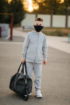 Een jongen staat op een sportveld na een training in de buitenlucht tijdens zonsondergang met een masker op