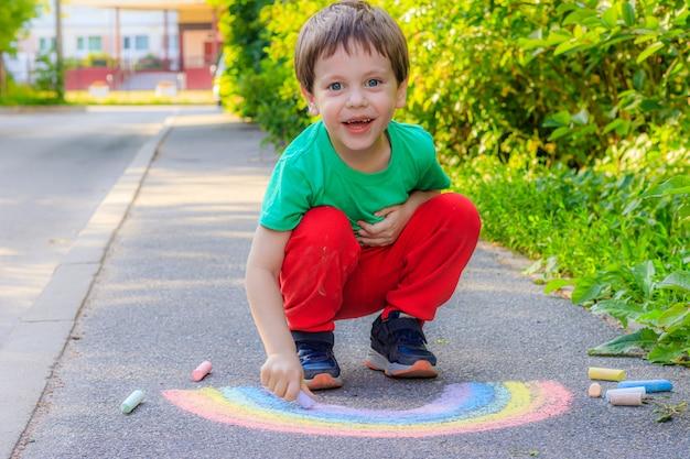 Een jongen tekent met kleurpotloden een regenboog op het asfalt