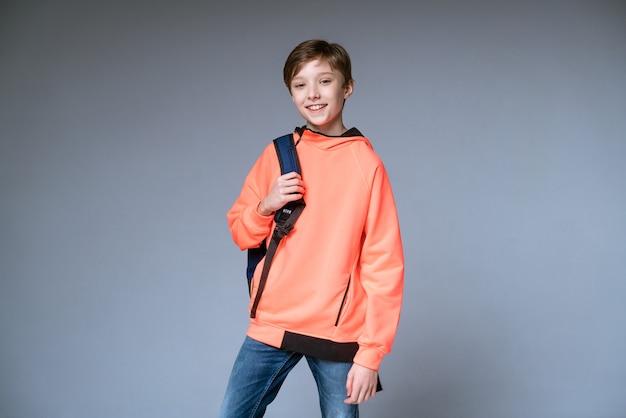 Een jongen tiener in een fel oranje trui poseren met een rugzak op een grijze muur gray
