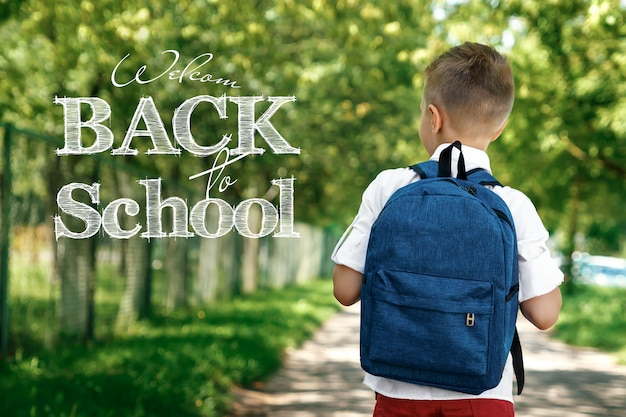 Een jongen uit een lagere school met een rugzak op straat