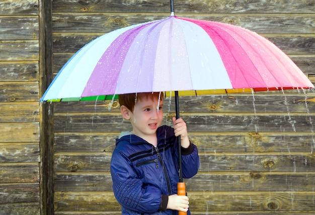 Een jongen van 5 jaar verstopt zich onder een paraplu voor de regen, emoties drukken angst en verrassing uit voor de komende grote regen