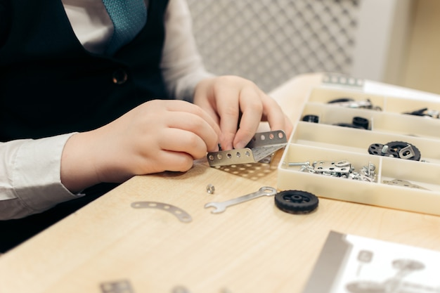Een jongen van 7 tot 8 jaar speelt in close-up met een metalen bouwpakket.