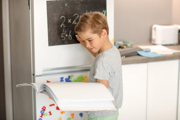 Een jongen van 8 jaar met een leerboek in zijn handen schrijft thuis op een lei.