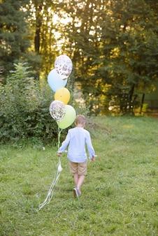 Een jongen van de basisschoolleeftijd rent met ballonnen. de jongen wijst met zijn rug naar de camera.