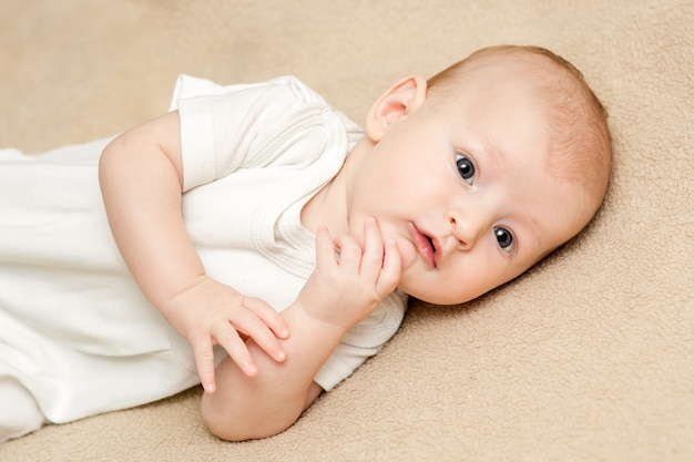 Een jongen van de portret leuke baby in witte kleren die op een beige bed liggen