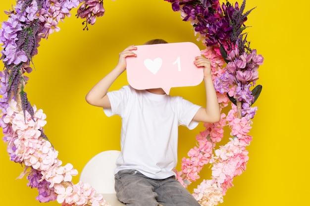Een jongen van het vooraanzicht de leuke kind in wit t-shirt en grijze jeans met witte tekenzitting op de bloem maakte tribune op het gele bureau