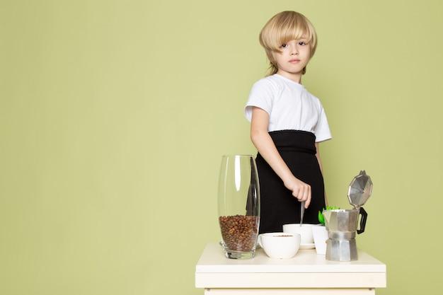 Een jongen van het vooraanzichtblonde in witte t-shirt dichtbij lijst die koffie op de steen gekleurde ruimte voorbereiden