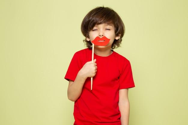 Een jongen van het vooraanzichtkind in de rode lippen van de t-shirtholding houdt op de steen gekleurde ruimte vast