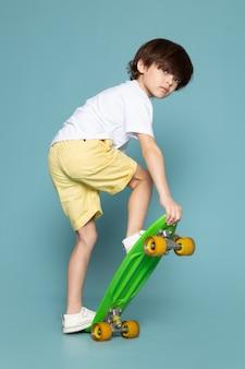 Een jongen van het vooraanzichtkind in witte t-shirt en gele jeans die groen skateboard berijden op de blauwe ruimte