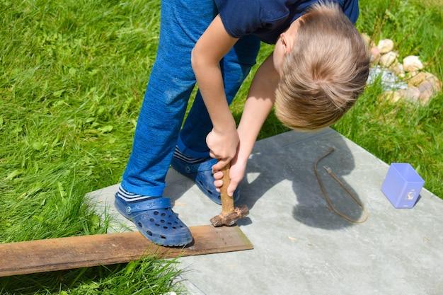 Een jongen werkt in de tuin. kinderwerkplaats buiten