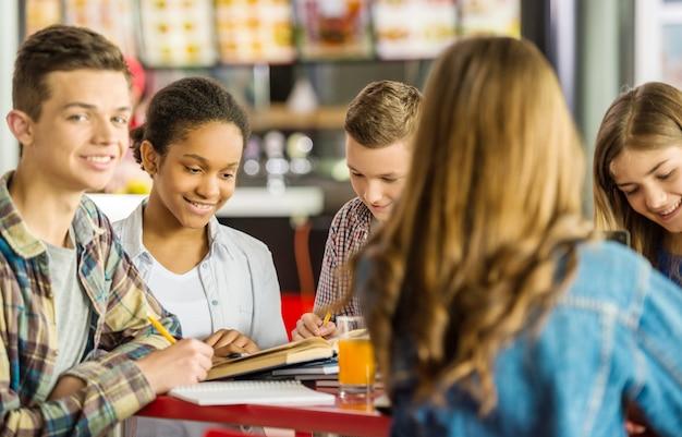 Een jongen zit aan een tafel met vrienden en studies.