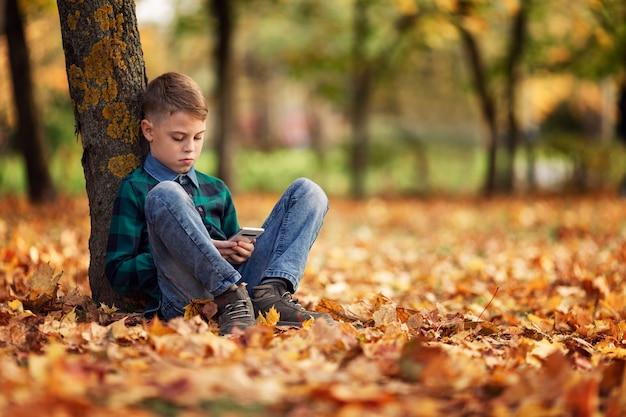 Een jongen zit in een herfstpark onder een boom met een telefoon in zijn handen