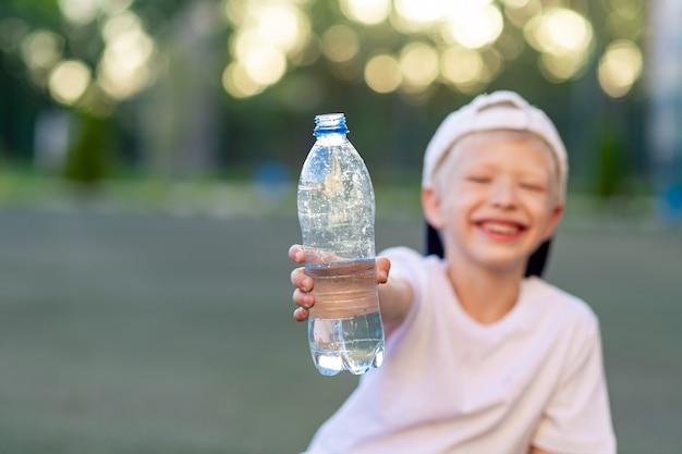 Een jongen zit op een groen gazon op een voetbalveld en houdt een fles water vast. focus op de waterfles