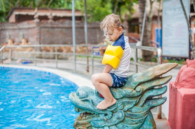 Een jongen zit op het aziatische beeld