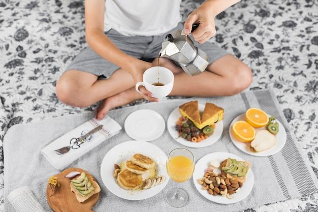 Een jongen zittend op bed met gekruiste been gieten koffie in de beker