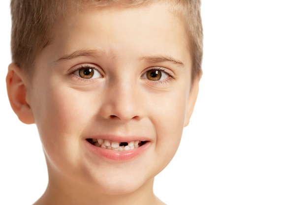 Een jongen zonder voortand glimlacht. geã¯soleerd op witte achtergrond.