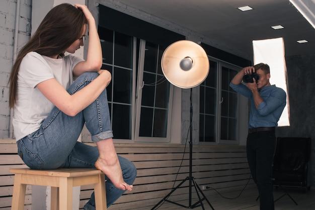 Een jongensfotograaf maakt foto's van een meisjesmodel in een studio