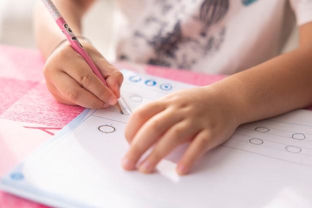 Een jongenshand schrijft huiswerk met een roze potlood op de tafel in de woonkamer van zijn huis