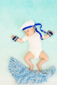 Een jongetje slaapt in een matrozenpakje en zwemt in zijn slaap op de golven
