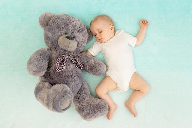 Een jongetje slaapt met een grote grijze teddybeer