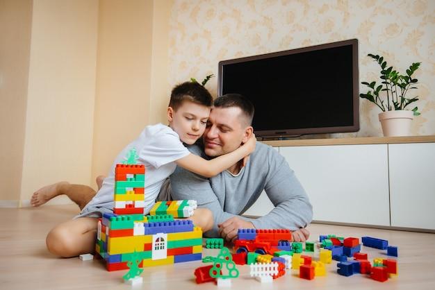Een jongetje wordt samen met zijn vader gespeeld door een aannemer en bouwt een huis. bouw van een gezinswoning.