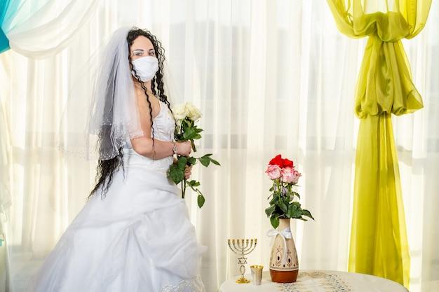 Een joodse bruid in een synagoge aan een tafel met bloemen voor een chuppa-ceremonie tijdens een pandemie, met een medisch masker en een boeket bloemen, wacht op de bruidegom. horizontale foto