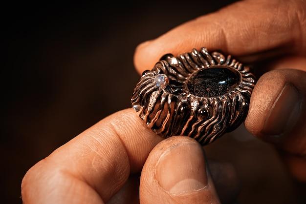 Een juwelier houdt een gouden ring met edelstenen vast.