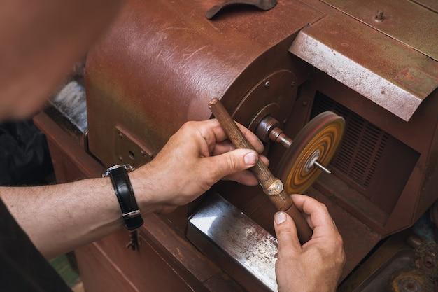 Een juwelier polijst een gouden ring op een machine in een werkplaats, een werkproces