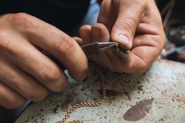 Een juwelier repareert een gouden ketting, corrigeert het slot met een tang, close-up