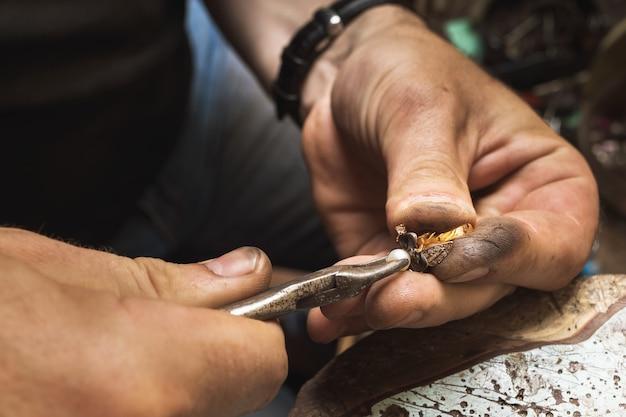 Een juwelier verwijdert parels van een gouden ring, houdt zich bezig met het demonteren ervan in een werkplaats, close-up