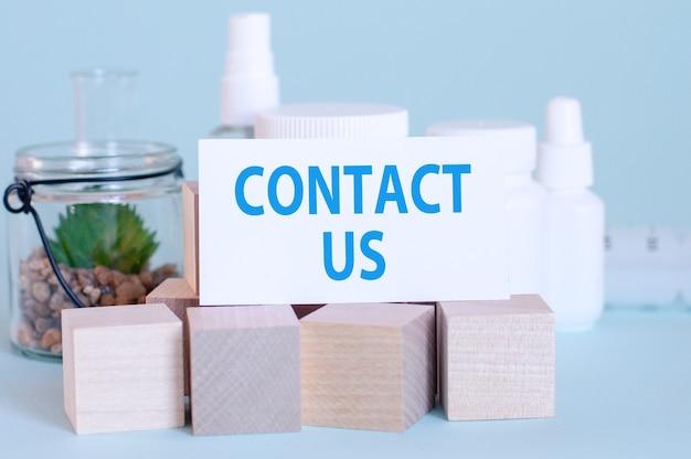 Een kaart met de inscriptie neem contact met ons op over de achtergrond van medicijnen en houten blokjes, blauwe achtergrond, selectieve aandacht
