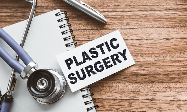 Een kaart met de tekst plastic chirurgie op de tafel van de houten dokter