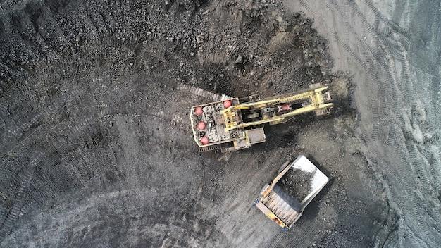 Een kabelgraafmachine laadt de overbelasting van de carrosserie van een mijnbouwtruck.