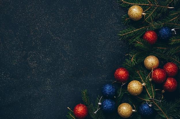 Een kader van groen spar en kerstmisspeelgoed op een zwarte achtergrond met lege ruimte