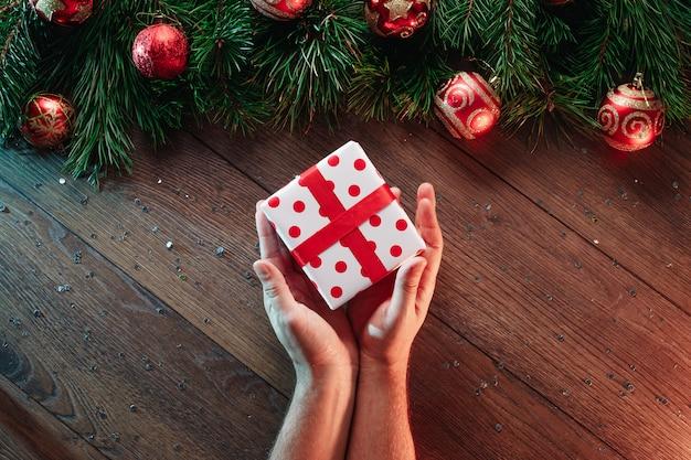 Een kader van pijnboomtakken en kerstmisdecoratie en handen die een gift op van een houten lijst geven. prettige kerstdagen en prettige feestdagen. uitzicht van boven.