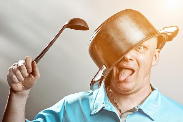 Een kale brutale man in blauw t-shirt zette een pot op zijn hoofd