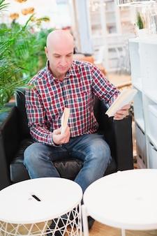 Een kale europese man in een geruit rood overhemd en blauwe spijkerbroek zit in een fauteuil in een licht appartement met groene planten, kiest boeken om in zijn vrije tijd te lezen. de mens houdt zich bezig met zelfontplooiing