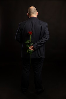 Een kale man in een pak houdt een rode roos achter zijn rug. volledige hoogte. Premium Foto