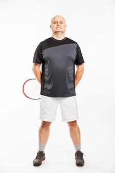 Een kale man in een volwassene in een sportuniform met een tennisracket.